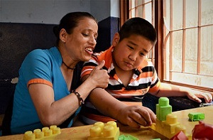 Autistic boy playing with his mother