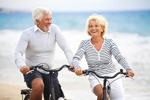 Older couple cycling along the beach
