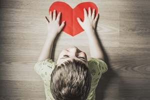 Boy placing hands on a red paper heart