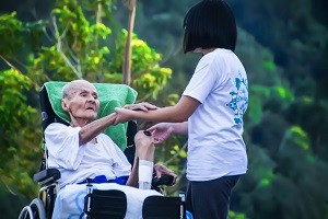 A care worker helping a patient in a lush garden
