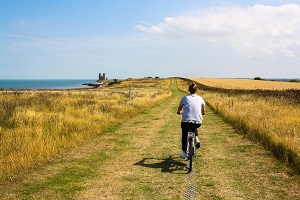 Woman cycling on coastal path
