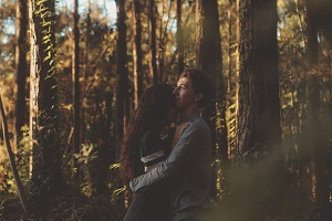 A young couple embracing in the forest