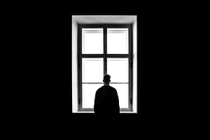 Man with depression staring out of a window