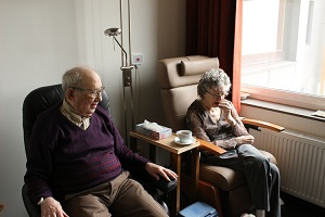An elderly couple sat in their care home accommodation
