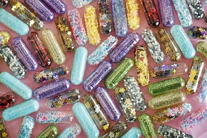 Vitamin capsules filled with colorful glitter