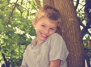 Autistic boy smiling by a tree