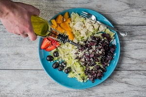 Olive oil poured over a salad as part of a ketogenic diet