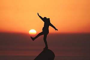 Man balancing on a mountain top at sunset