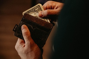 Man taking dollar bills out of his wallet