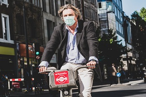 Man cycling wearing a mask in a polluted city
