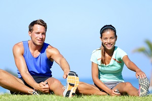 Man and woman in sports clothing stretching off