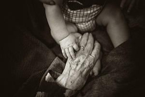 An old lady holding her great-grandchild's hand
