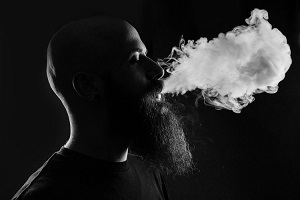 Bearded man blowing out cigarette smoke