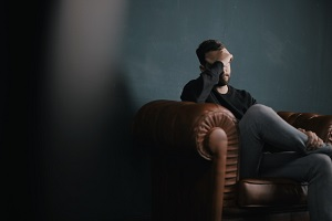 Man sitting on sofa looking stressed