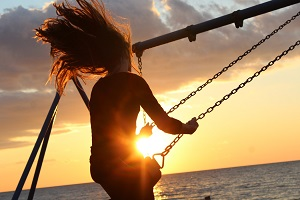 A woman on a swing at sunset