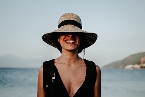 A woman with a big smile by the sea