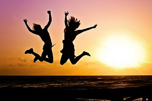 Two young women jumping with joy at sunset